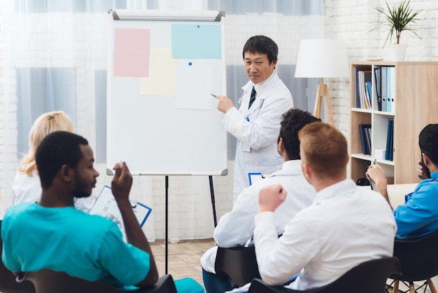 Asiatischer doktor teilt erfahrung mit kollegen.