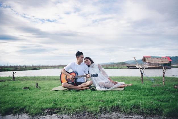 Asiatischer ehemann, der gitarre spielt und genießen mit seinem asiatischen konzept des verheirateten paars und der familie der schwangeren frau im freien.