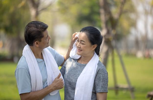 Asiatischer ehemann des glücklichen älteren paares, der schweiß vom gesicht der frau abwischt, nachdem er im freiluftpark gelaufen ist.