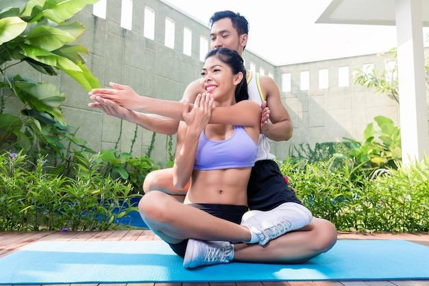 Asiatischer eignungstrainer, der sport mit frau ausübt