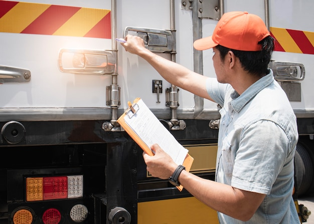 Asiatischer ein lkw-fahrer, der klemmbrett seine überprüfende sicherheitsfrachtcontainer-stahltür hält.