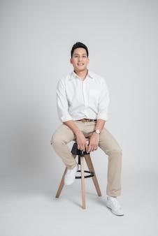 Asiatischer entspannender mann beim sitzen auf dem stuhl