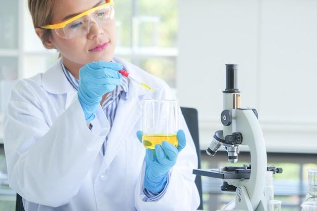 Asiatischer ernster weiblicher chemiker, der im labor arbeitet