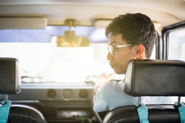 Asiatischer fahrer, der ein weinleseauto fährt und zurück vom spiegel schaut.