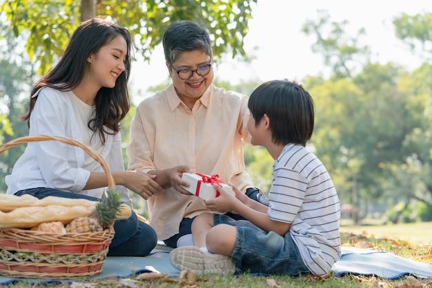 Asiatischer familienjunge und -mutter, die großmutter geschenkbox während des picknicks im park geben