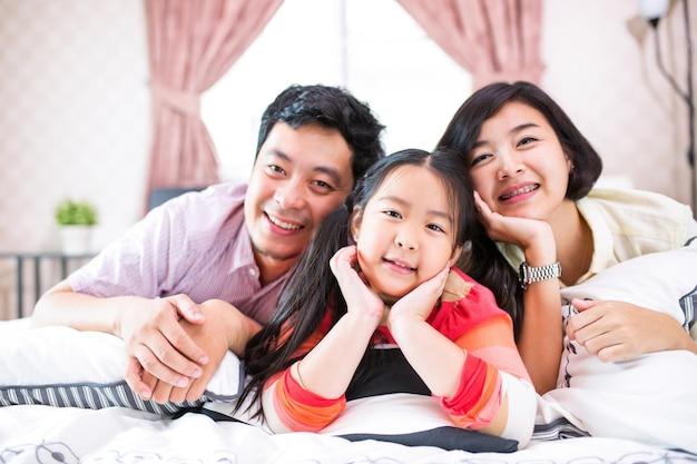 Asiatischer familienlebensstil, der im schlafzimmer lächelt.