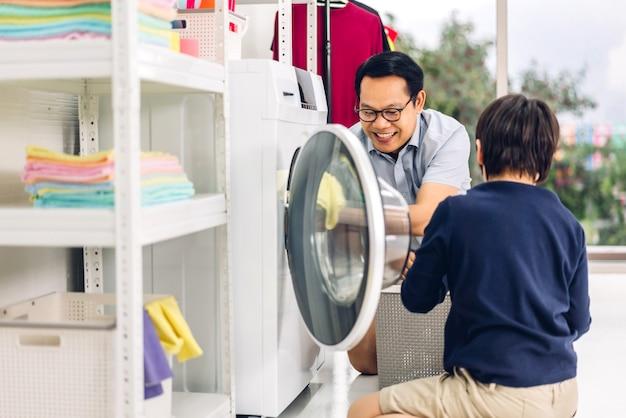 Asiatischer familienvater und kleiner sohn des kleinen jungen, die spaß haben, hausarbeiten zu tun, die schmutzige wäsche in der waschmaschine zusammen in der waschküche zu hause machen