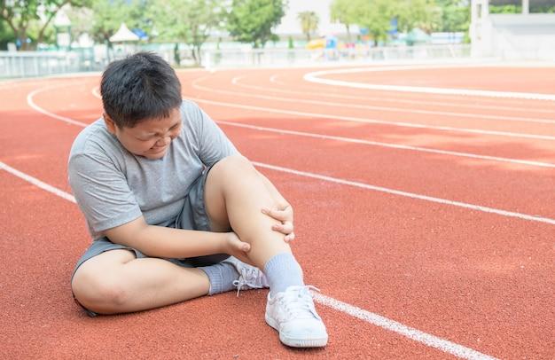 Asiatischer fetter junge, der seine sportbeinverletzung hält. muskelschmerzen