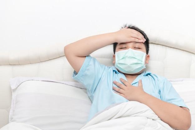 Asiatischer fetter junge tragen chirurgische maske mit hohem fieber und brustschmerzen auf bett,