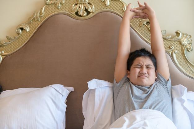Asiatischer fetter junge wacht auf und streckt sich am morgen auf dem bett, gesundes konzept