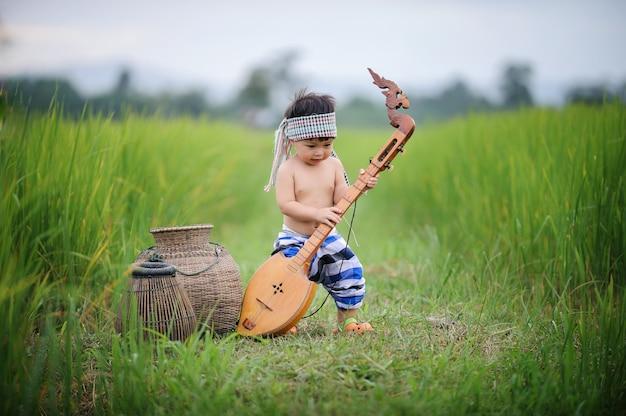 Asiatischer fischenjunge, der eine hölzerne mandoline auf dem grünen reisgebiet an der countyseite von spielt