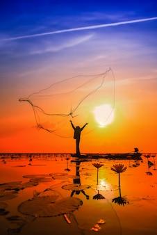 Asiatischer fischer auf bootsfischen am see