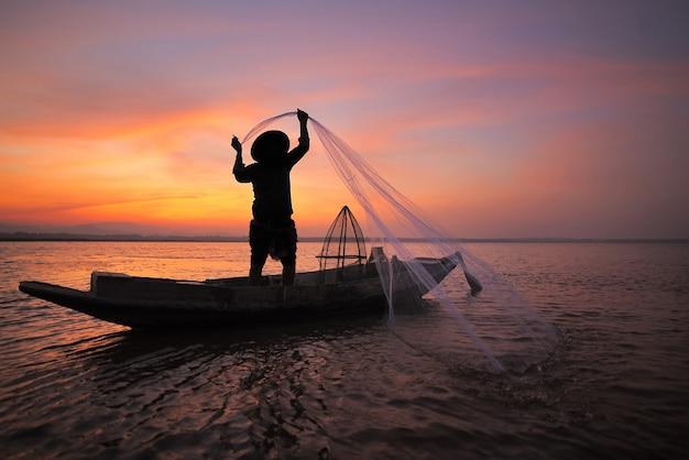 Asiatischer fischer mit seinem hölzernen boot im naturfluß am frühen morgen vor sonnenaufgang