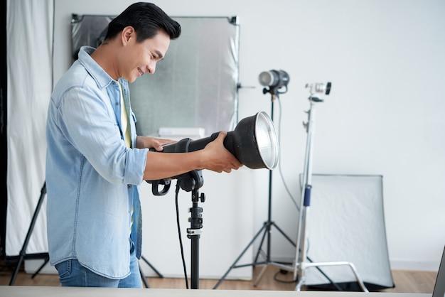 Asiatischer fotograf, der beleuchtung im berufsstudio gründet