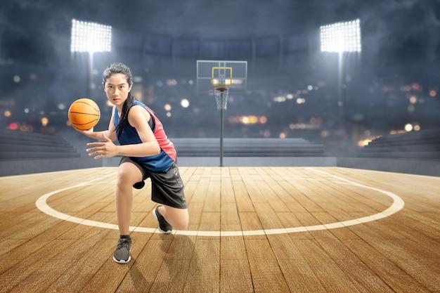 Asiatischer frauenbasketballspieler in der aktion mit der kugel