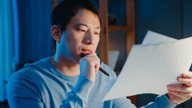 Asiatischer freiberuflicher geschäftsmann fokussiert arbeitstyp auf laptop-computer beschäftigt mit voller papierkramkarte auf schreibtisch im wohnzimmer