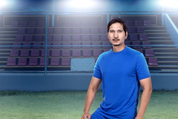 Asiatischer fußballspielermann im blauen trikot, der auf dem fußballplatz steht