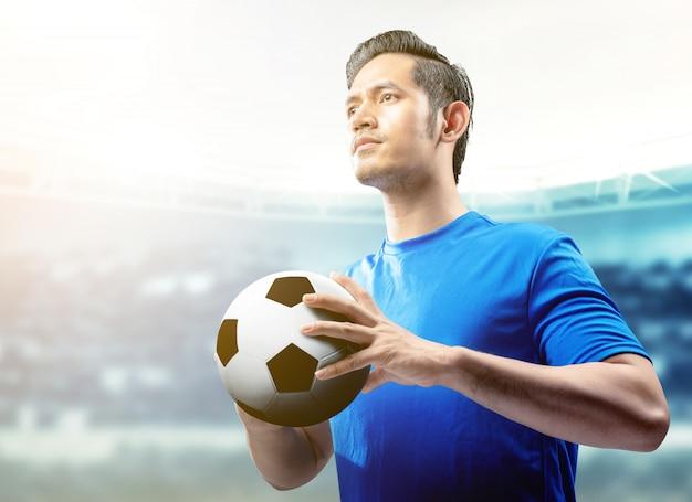 Asiatischer fußballspielermann im blauen trikot, welches den ball auf dem fußballplatz hält