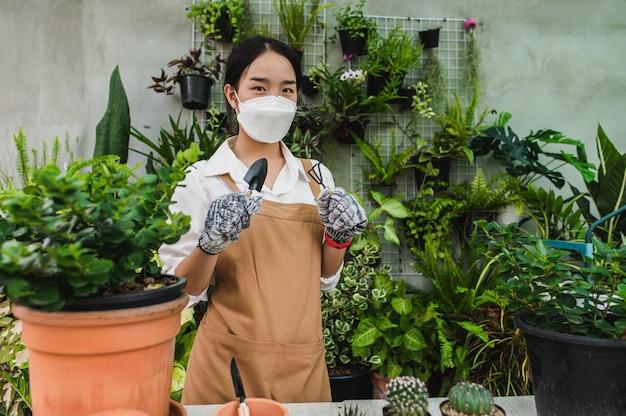Asiatischer gärtner, der gesichtsmaske und schürzenständer trägt und eine schaufel zeigt