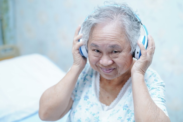 Asiatischer geduldiger gebrauchskopfhörer der älteren frau beim sitzen auf bett im krankenhaus.