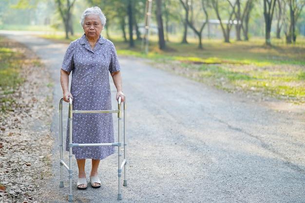 Asiatischer geduldiger weg der älteren frau mit wanderer im park.