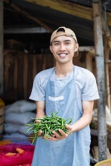 Asiatischer gemüseverkäufermann lächelt, während er grüne chilis am gemüsestand hält