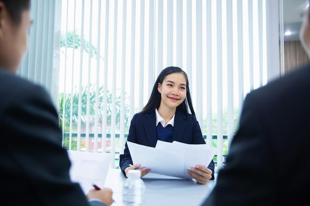 Asiatischer geschäftsfraukandidat, der ihre profilbewerbung auf vorstellungsgespräch darstellt