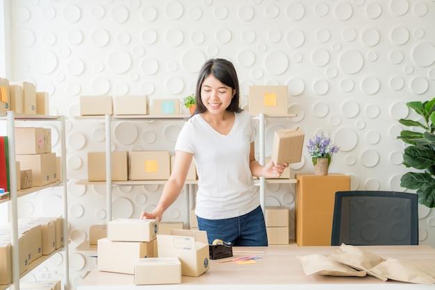 Asiatischer geschäftsinhaber, der zu hause mit packbox am arbeitsplatz arbeitet