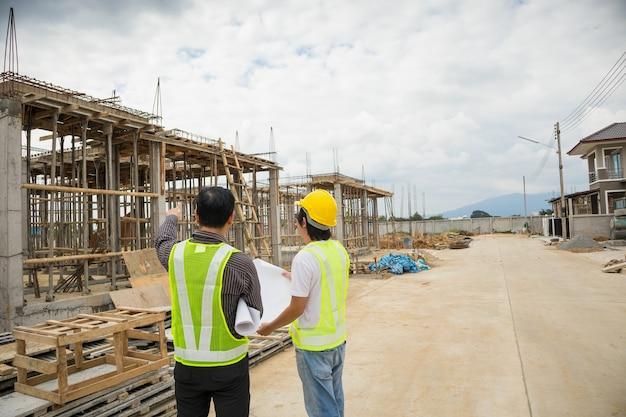 Asiatischer geschäftsmann-bauleiter und ingenieurarbeiter im schutzhelm halten blaupausenpapier zur hand auf hausbaustelle