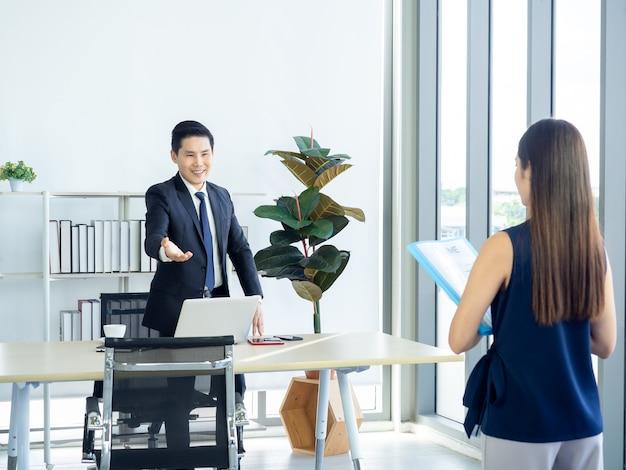 Asiatischer geschäftsmann, chef im anzug, der handgeste macht, um junge frau mit lebenslauf im vorstellungsgespräch einzuladen, sich auf den stuhl zu setzen