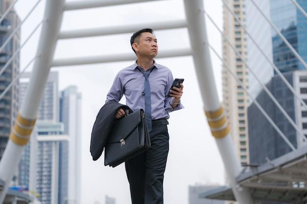 Asiatischer geschäftsmann, der aktenkoffer mit geschäftslokalgebäuden geht und hält