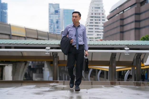 Asiatischer geschäftsmann, der aktenkoffer mit geschäftslokalgebäuden im stadthintergrund geht und hält