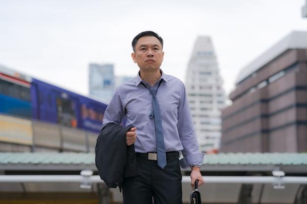 Asiatischer geschäftsmann, der aktenkoffer mit geschäftslokalgebäuden in der stadt geht und hält