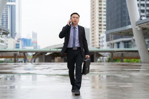Asiatischer geschäftsmann, der am handy hält aktenkoffer geht und spricht