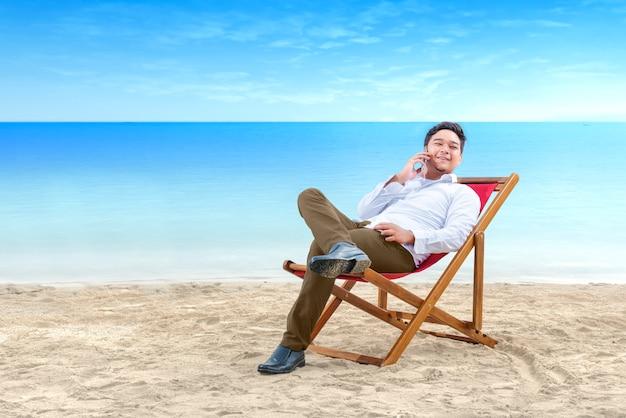 Asiatischer geschäftsmann, der am handy spricht, während sie sich zurück im strandstuhl auf strand lehnen