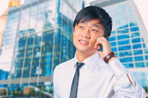 Asiatischer geschäftsmann, der am mobilhandy spricht