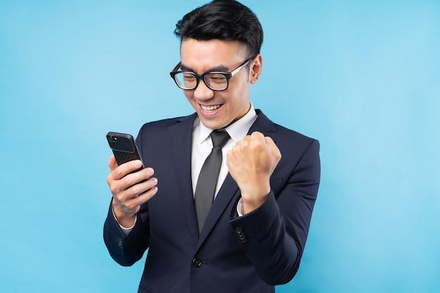 Asiatischer geschäftsmann, der anzug mit smartphone trägt und sieg fühlt