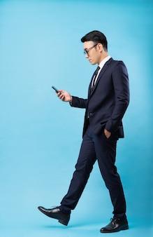 Asiatischer geschäftsmann, der anzug trägt und auf blaue wand geht
