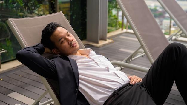 Asiatischer geschäftsmann, der anzug trägt und sich im freien entspannt, während er sich auf der sonnenliege in der stadt niederlegt?