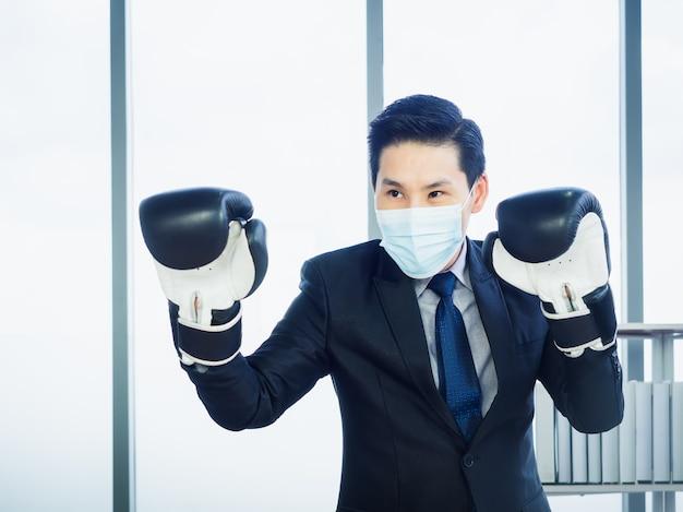Asiatischer geschäftsmann, der anzug und schützende gesichtsmaske und hand trägt, die boxhandschuhe im büro tragen