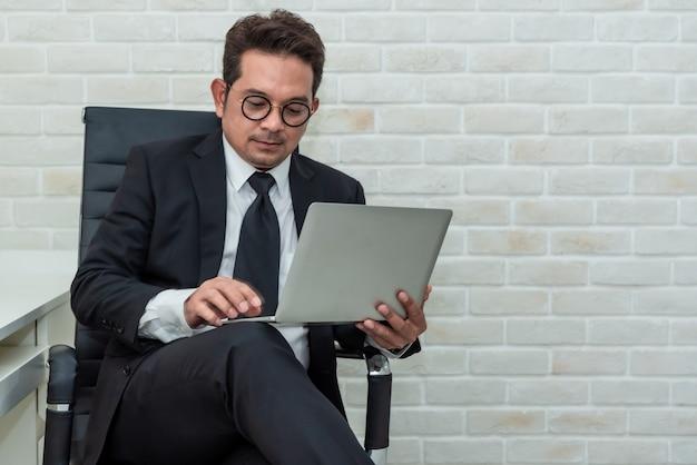Asiatischer geschäftsmann, der auf dem arbeiten an laptop sitzt.