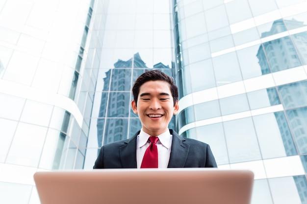 Asiatischer geschäftsmann, der auf laptop vor turmgebäude arbeitet