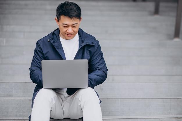 Asiatischer geschäftsmann, der auf treppen sitzt und am computer arbeitet