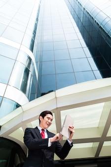 Asiatischer geschäftsmann, der außenmails auf tablet-computer vor turmgebäude prüft