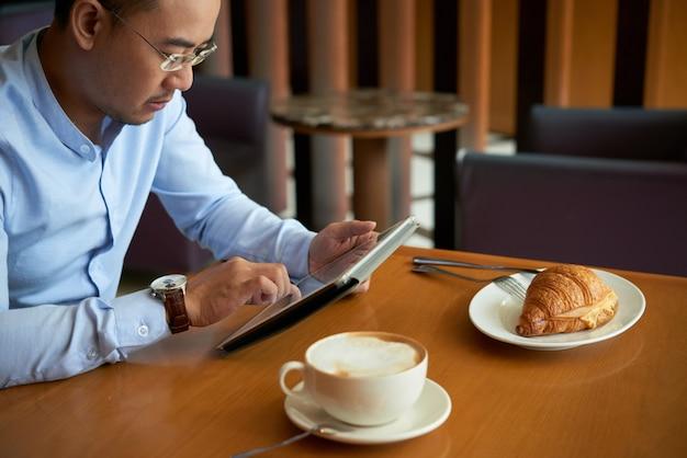 Asiatischer geschäftsmann, der das hörnchen und den kaffee durchstöbert das netz auf tragbarem gerät isst