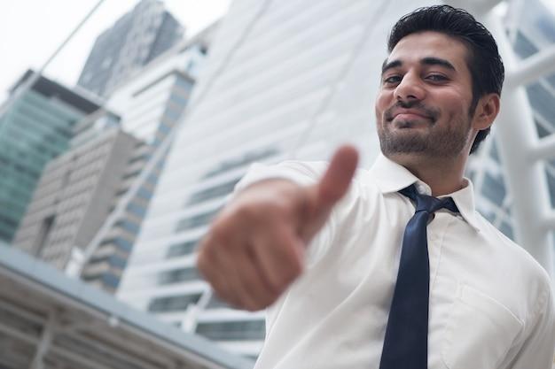 Asiatischer geschäftsmann, der daumen herauf geste zeigt; porträt eines asiatischen, nordindischen erfolgreichen und selbstbewussten geschäftsmannes zeigt seine zustimmung, ja, ok daumen hoch
