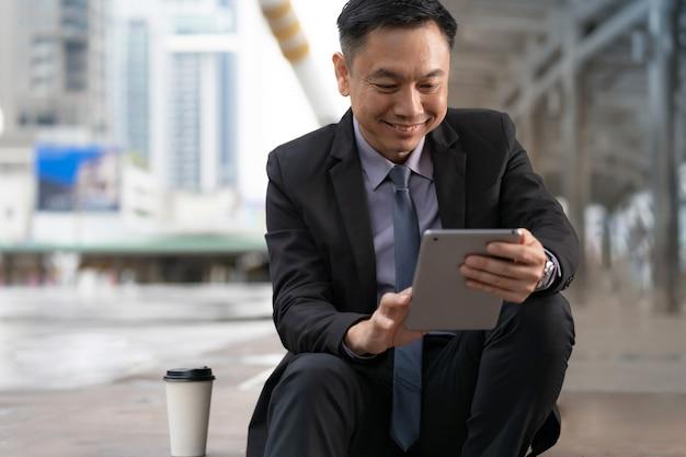 Asiatischer geschäftsmann, der digitale tablette mit geschäftslokalgebäuden in der stadt sitzt und hält