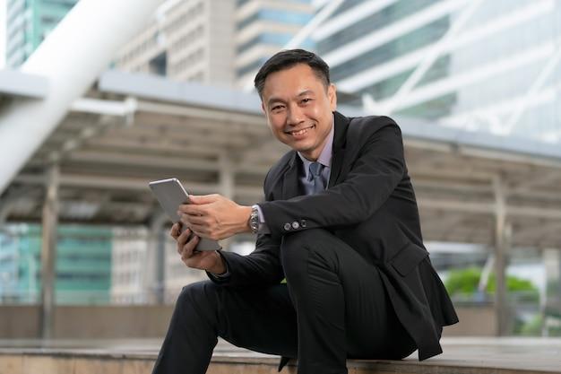 Asiatischer geschäftsmann, der digitale tablette mit geschäftslokalgebäuden sitzt und hält