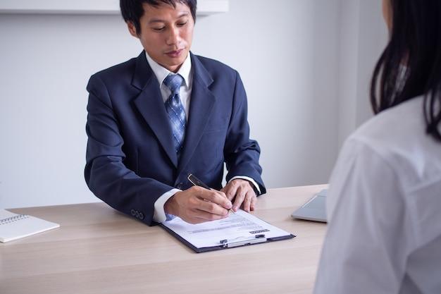 Asiatischer geschäftsmann, der einen neuen angestellten interviewt. der personalleiter erkundigt sich nach der beruflichen laufbahn und den fähigkeiten der bewerber. bewerbungsgesprächskonzept
