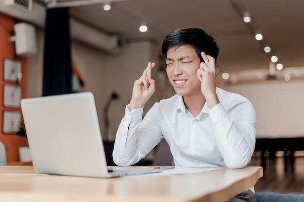 Asiatischer geschäftsmann, der finger gekreuzt mit laptop hält